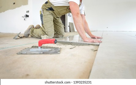 Craftsman on his knees working in a new building on the ground, laying glazed ceramic tiles - selective focus, lot of copy space