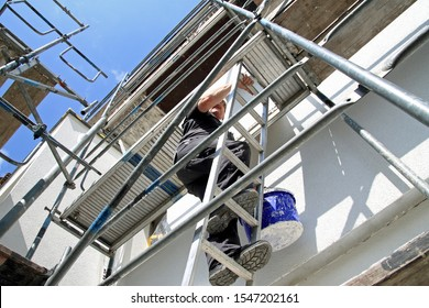 Craftsman on a scaffolding is climbing to renovate a house