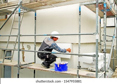 Craftsman on a scaffolding, mounted heat insulation system