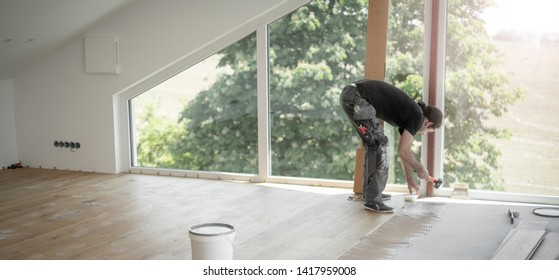 Craftsman puts parquet floor and hits the the bat with the hammer to put the floorboards together