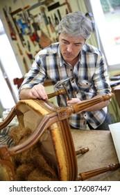 Craftsman repairing antique armchair in workshop