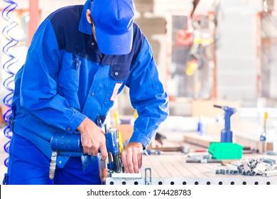 Craftsman rivet metal with air compressed pistol in workshop