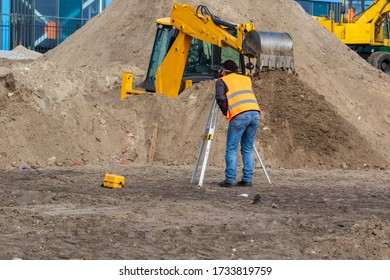 A craftsman is standing at a construction site near surveying equipment. A special device for surveyors before carrying out earthwork. Excavator digs land for the construction of a new park area.