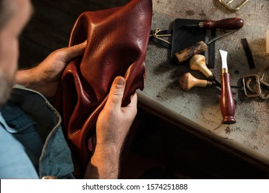 Craftsman touching leather, close-up. A raw material, stuffs and preparation of leather craft work