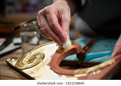 Craftsman uses a cotton pad during the gilding process tecnique.