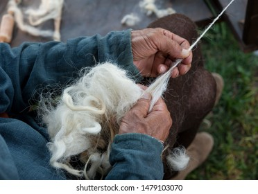 Craftsman using an old spinning wheel to turn wool into yarn.