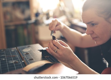 Craftsman woman works with decoration, makes the base of copper metal under the enamel, the concept of a home workshop and creativity. Back light, soft focus and toning