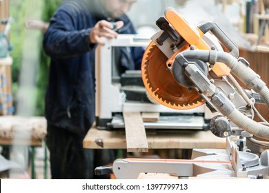 Craftsman woodworking at carpentry with lots of modern professional power tools. Man using thicknessing machine and circular saw and other equipment at workshop