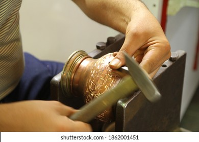 craftsman working with hammer during hand stamping or engraving decoration pattern on metal plate