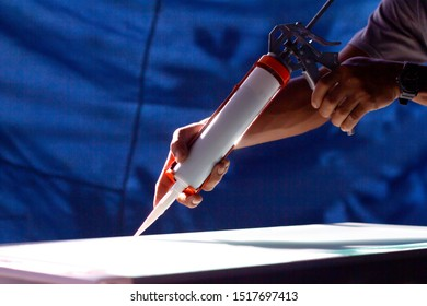 The craftsman's hand uses a silicone caulking gun for general and industrial applications.