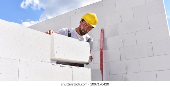 craftsmen at home construction - bricklayers working in work clothes