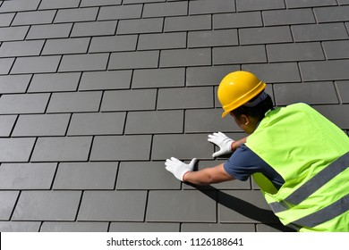 Craftsmen are installing a roof home.Professional roof workers with safety equipment installing roof tile for a new house property project.Working on rooftop.