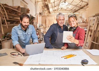 Craftsmen team with computers in a carpenter's workshop in a medium-sized craft business