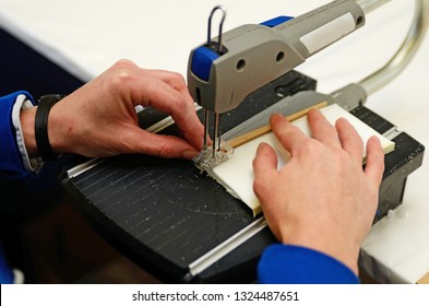 A craftswoman cuts out a piece of plastic foam with a small band saw while making stage props in a commercial sewing room.
