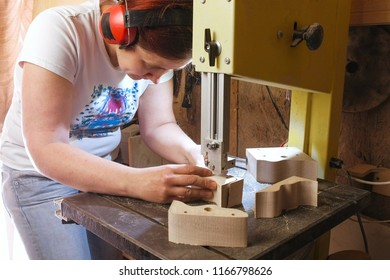 Craftswoman is cutting a wood toy cars workpiece from wood with bandsaw.
