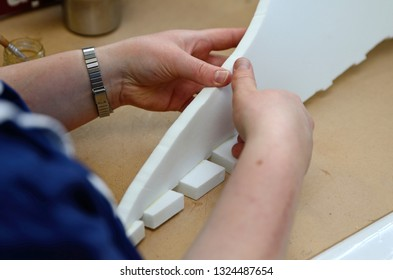 A craftswoman glues together pieces of plastic foam while making stage props in a commercial sewing room.