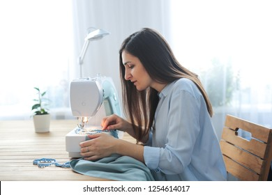 craftswoman with long black hair sews on a sewing machine in her home workshop, a real room in the Scandinavian style, a concept of a hobby and handicraft.