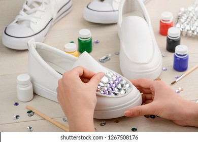 Craftswoman putting rhinestones on shoes. Making simple white slip-ons look gorgeous. Custom design, DIY concept.