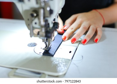 craftswoman searching for ideas in internet using gadget, seamstress wants to make extraordinary leather belt. Black-haired girl with ponytail wearing comfortable grey T-shirt sitting near table with