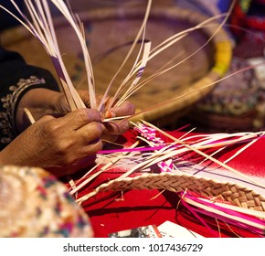 A craftswoman weaving a baskets from palm leaves