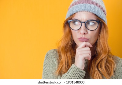 Crafty young woman thinking. Closeup portrait of smart person, isolated on yellow background. Close-up girl looking to side. Studio shot