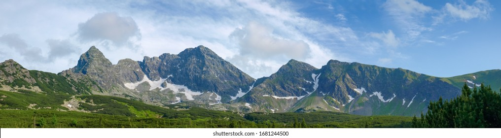 Craggy mountain range against the sky and forest at the foot of the ridge in valley on a foreground, Tatra Mountains, panoramic view