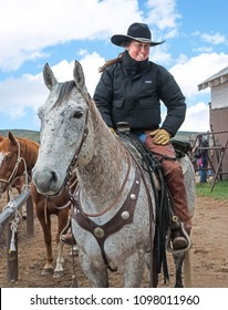 Craig, CO April 29, 2016: Cowgirl wrangler is saddled up on her spotted appaloosa horse and ready to go on annual horse drive trail ride
