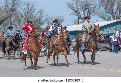 Craig, CO, USA - May 6, 2018: Rex Walker owner of Sombrero Ranch and Miss Colorado Rodeo 2018 gallop down main street in Maybell, CO during annual Great American Horse Drive parade