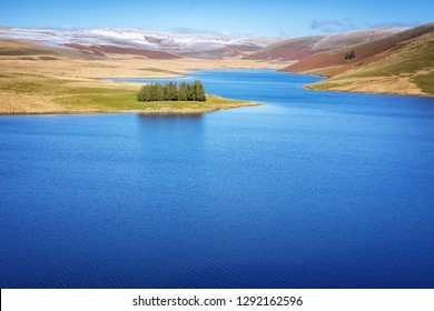 Craig Goch resevoir in Elan Valley Wales with snow topped mountains and trees. Water to supply birmingham reflecting blue sky