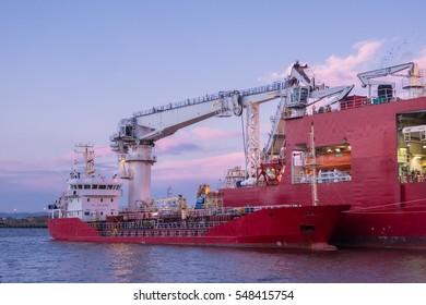 Craine ship loading cargo from a bigger ship in Edinburgh's Leith Docks. Scotland, United Kingdom