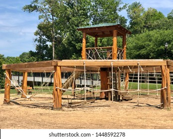 Cramerton, NC - July 4, 2019: Wooden playground with ropes for kids to play on the Goat Park and Greenway.