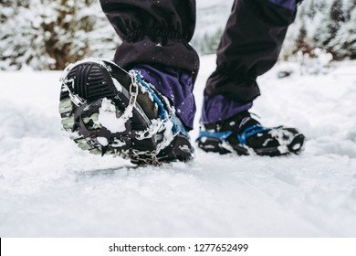 Crampons on hiking boots. Close up view on shoes on snowy path