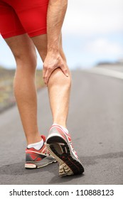 Cramps in leg calves or sprain calf on triathlete runner. Sports injury concept with running man.