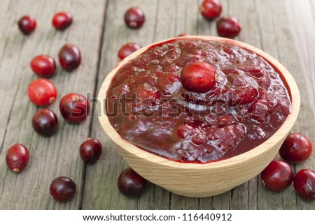 Cranberries jam in bowl on wooden boards