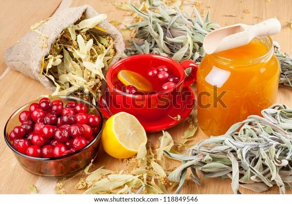cranberries, jar with honey, fruit tea cup, healing herbs and lemon