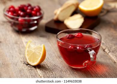 cranberries lemon ginger drink in a glass cup, honey, half a lemon, slices of ginger on old wooden background