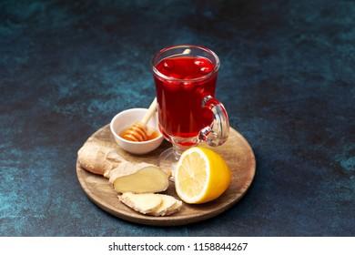 cranberries lemon ginger drink in a glass cup, honey, half a lemon, slices of ginger on a blue background
