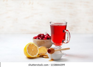 cranberries lemon ginger drink in a glass cup, honey, half a lemon, slices of ginger on a white background