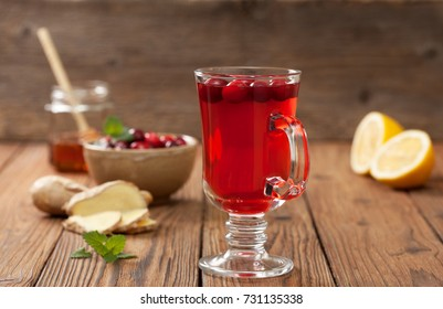 cranberries lemon ginger drink in a glass beaker, cranberries in a bowl, half a lemon, slices of ginger on an old wooden background