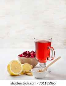 cranberries lemon ginger drink in a glass cup, cranberries in a bowl, half a lemon, slices of ginger on a white  background