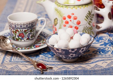 Cranberries in powdered sugar in a vase, a cup and a teapot on the table