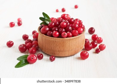 Cranberries in wooden bowl on wooden table
