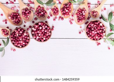 cranberries in wooden cups and spoons on white background top view. background with cranberries. copy space. flat lay.