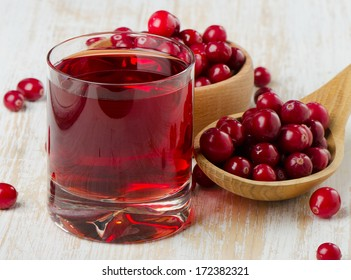 Cranberries in a  wooden spoon and glass of juice. Selective focus