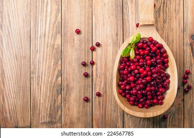 cranberries in wooden spoon on table