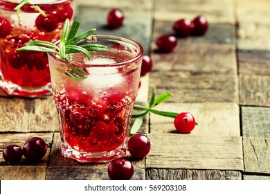 Cranberry beverage with ice and berries, vintage wooden background, selective focus