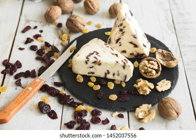 Cranberry cheese served on round slate board with dried cranberry, raisin and walnut, wooden table. Traditional british cheese