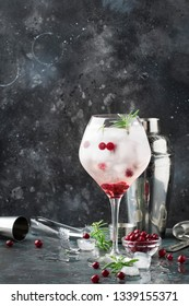 Cranberry cocktail with ice, rosemary and berries in big wine glass, bar tools, gray bar counter background, top view