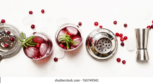 Cranberry cocktail with ice, rosemary and berries, bar tools, white background, banner, top view