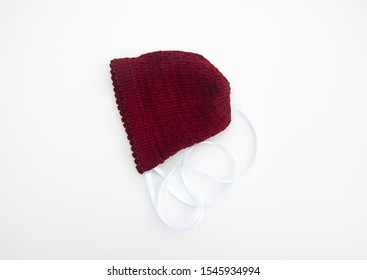 Cranberry colored baby bonnet knit isolated on a light background.  Baby hat has white satin ribbon.